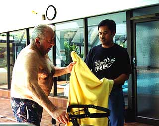 Guy at swimming pool receiving a towel